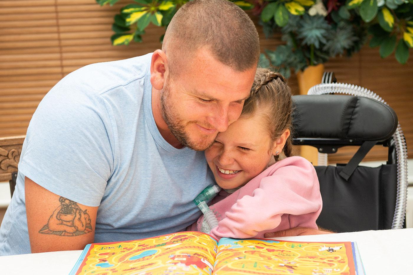 A girl with a ventilator hugs her dad whilst sitting a dining room table